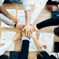 Crop coworking business people stacking hands above wooden desk with paper documents
