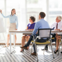 Cheerful young businesswoman pointing at whiteboard and explaining strategy. Confident business coach presenting project to staff. Colleagues listening to presenter. Business meeting concept